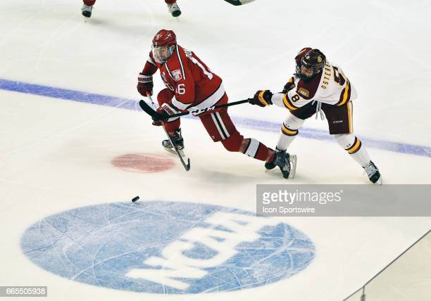 Harvard Crimson forward Ryan Donato puck handles against MinnesotaDuluth Bulldogs wing Kyle Osterberg NCAA Frozen Four semifinal game with the...