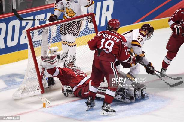 Harvard Crimson goalie Merrick Madsen falls backwards into the net in the second period of an NCAA Frozen Four semifinal game with the Harvard...