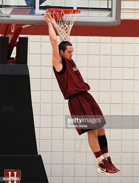 Harvard Crimson guard Laurent Rivard swings from the rim at practice