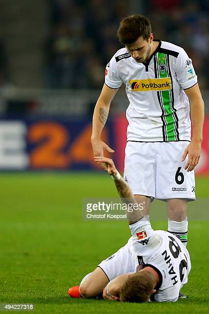 Harvard Nordtveit of Moenchengladbach cares of Andre Hahn of Moenchengladbach lying on the pitch after an injury during the Bundesliga match between...