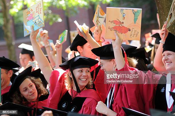 Harvard University students at the School of Education hold up books as their degree is announced during commencement ceremonies June 4 2009 in...