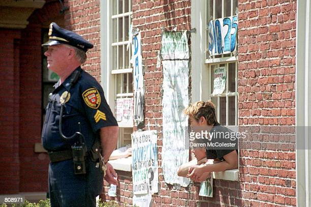 Harvard University students peer out a window of Massachusetts Hall May 3 2001 at the university in Cambridge MA A student 'sit in' is in it's...