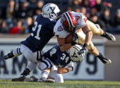 Harvard University tight end Kyle Juszczyk sails for some yardage after a catch as Yale University's Collin Bibb #21 and John Powers #34 try to bring...