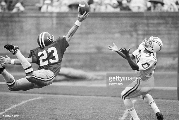 Harvard's Bill Emper sails through the air to knock the ball away from Dartmouth's Jimmie Solomon who waits with outstretched hands during 2nd...
