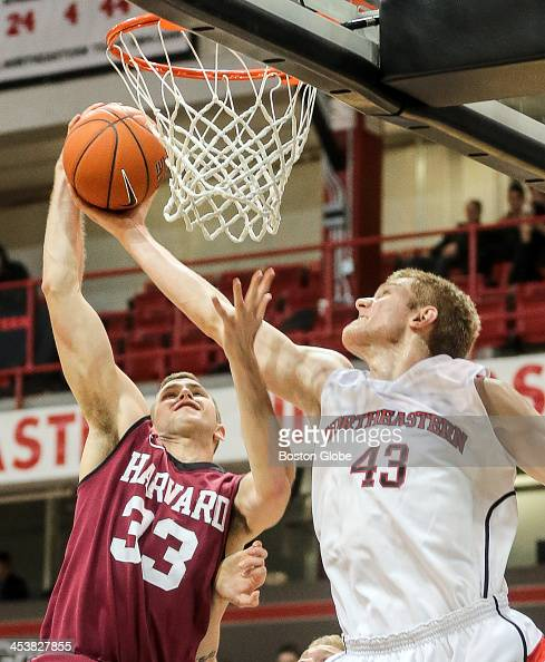Harvard's Evan Cummins tries to stop Northeastern's Scott Eatherton from scoring during a basketball game between Northeastern University and Harvard...