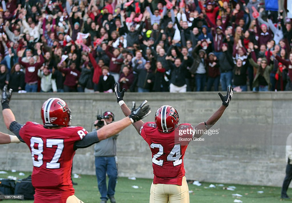 Harvard's Treavor Scales celebrates with fans in the end zone his long fourth quarter touchdown to seal the win for Harvard as Harvard University hosts Yale University during their annual game, Nov. 17, 2012 at Harvard Stadium. Harvard's Cameron Brate is at left.