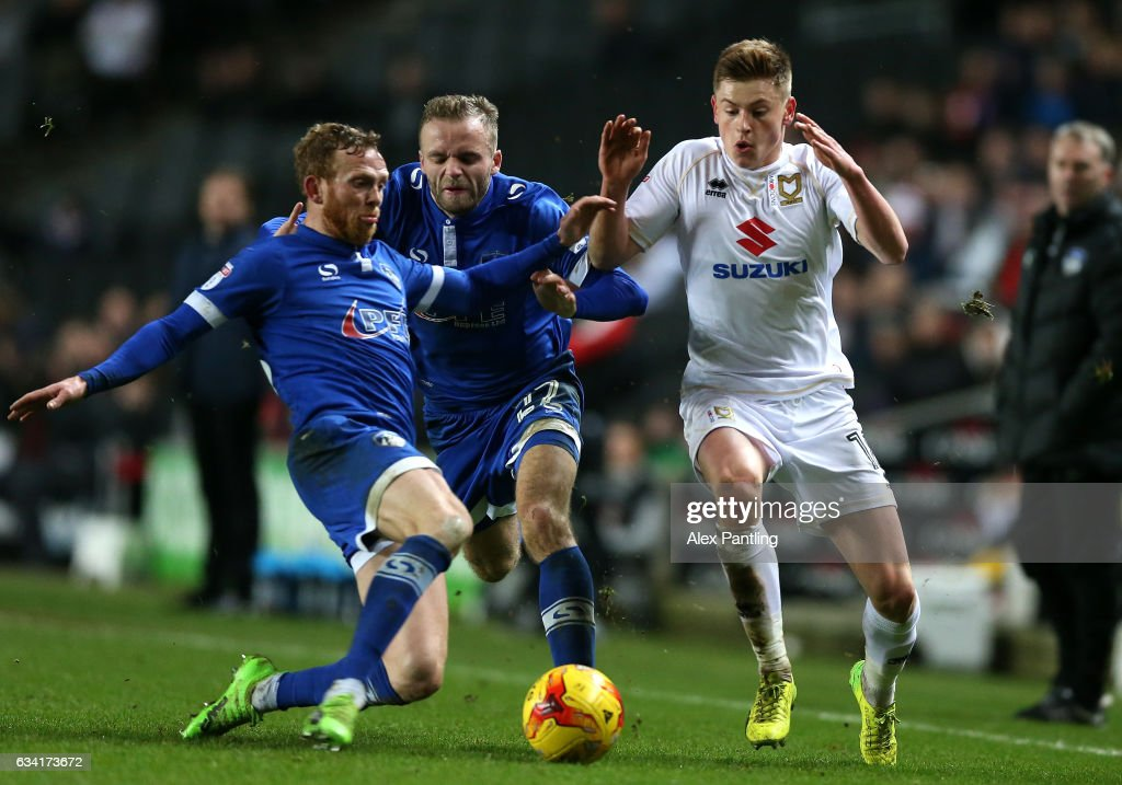 Harvey Barnes of MK Dons rides a tackle from Paul Green of Oldham Athletic (L) during the Sky Bet League One match between Milton Keynes Dons and Oldham Athletic at StadiumMK on February 7, 2017 in Milton Keynes, England.