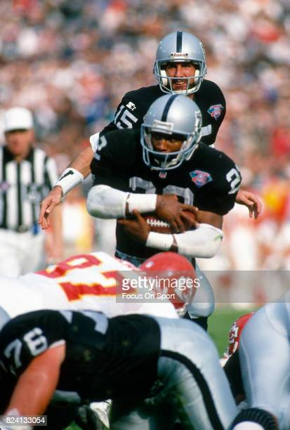 Harvey Williams of the Los Angeles Raiders get hit by Dan Saleaumua of the Kansas City Chiefs during an NFL Football game December 24 1994 at the Los...