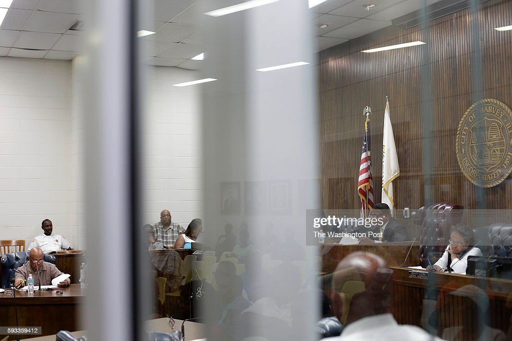 Harvey's Police Chief Denard Eaves left listens as Harvey Mayor Eric Kellogg second from right addresses a city council meeting at City Hall as City...