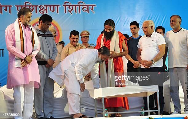 Haryana Health Minister Anil Vij touching the feet of Yoga Guru Baba Ramdev during the Yoga training camp organized by Baba Ramdev's Patanjali...