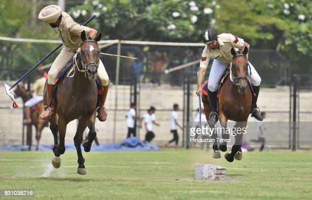 Haryana Police officials show horse riding skills during a full dress rehearsal for the upcoming Independence Day celebrations at Tau Devi Lal...