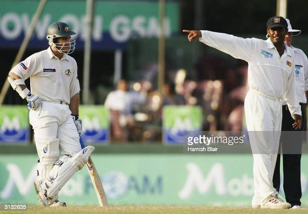 Hashan Tillakaratne of Sri Lanka and Justin Langer of Australia look on Langer has been charged with bringing the game into disrepute after...