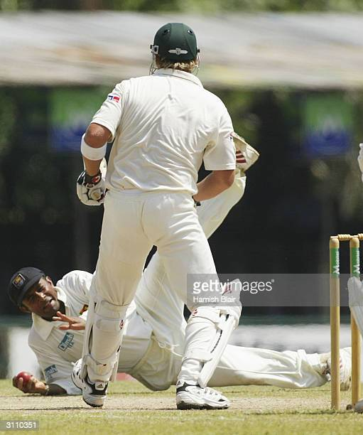 Hashan Tillakaratne of Sri Lanka dives for the ball with Shane Warne of Australia looking on during day four of the Second Test between Australia and...