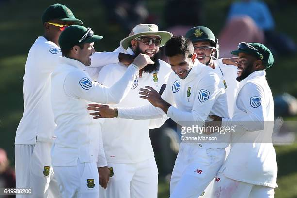 Hashim Amla celebrates with team mates the dismissal of Henry Nicholls of New Zealand during day two of the First Test match between New Zealand and...