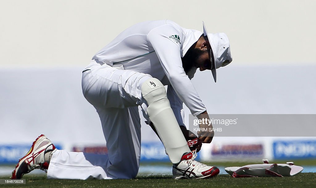 Hashim Amla of South Africa adjusts his pads on the second day of their first Test against Pakistan at the Sheikh Zayed Cricket Stadium in Abu Dhabi on October 15, 2013. Pakistan reached 77-0 at lunch in reply to South African first innings score of 249 all out.