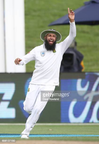 Hashim Amla of South Africa celebrates after Wicketkeeper Quinton de Kock takes the wicket of Jeet Raval of New Zealand between New Zealand and South...