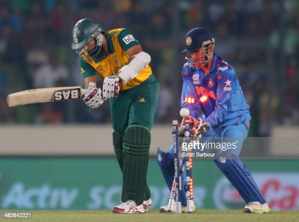 Hashim Amla of South Africa is out bowled as MS Dhoni of India looks on during the ICC World Twenty20 Bangladesh 2014 2nd SemiFinal match between...