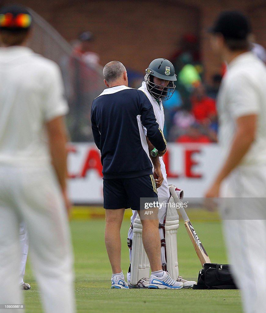 Hashim Amla of South Africa (C,R) receives medical attention after being hit by the ball on the first day of the second and final cricket test match between South Africa and New Zealand at the AXXESS St George's Stadium in Port Elizabeth, South Africa. AFP PHOTO / Anesh Debiky