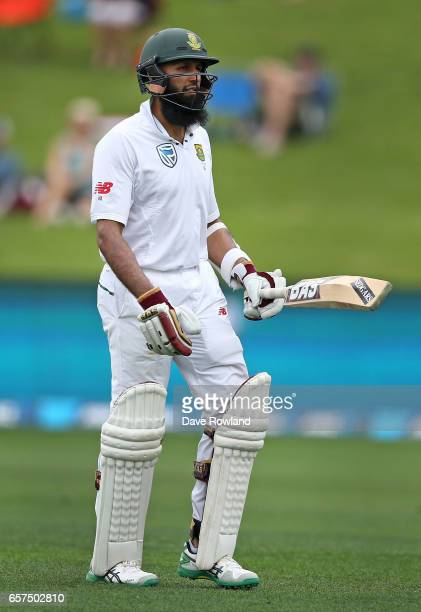 Hashim Amla of South Africa walks after being bowled by Colin de Grandhomme of New Zealand during day one of the Test match between New Zealand and...