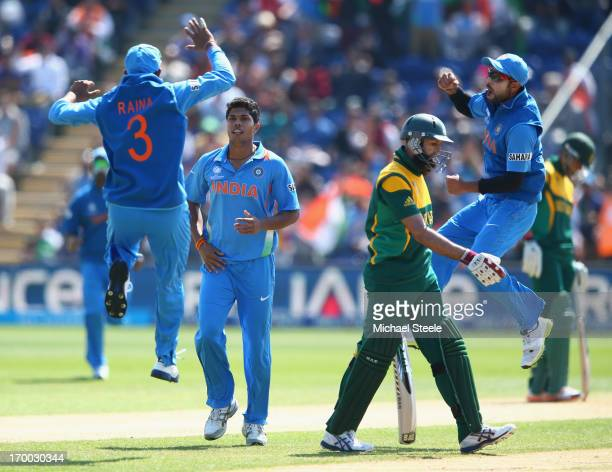Hashim Amla of South Africa walks as Umesh Yadav of India captures his wicket as Suresh Raina and Virat Kohli celebrate during the Group B ICC...