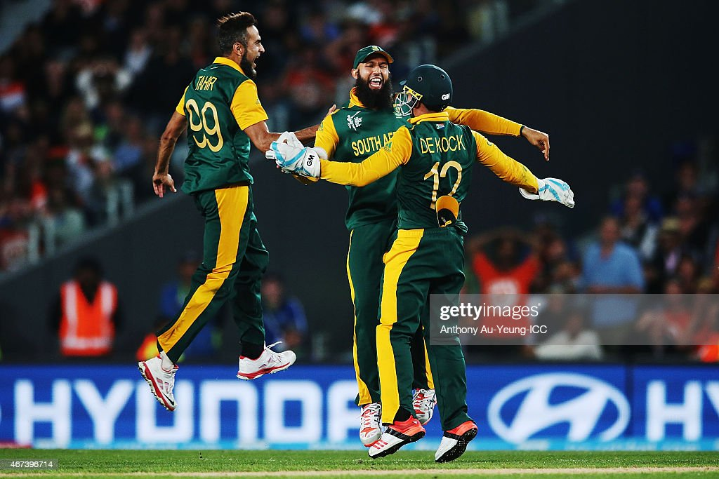 Hashim Amla, Quinton de Kock and Imran Tahir of South Africa celebrate the runout of Martin Guptill of New Zealand during the 2015 Cricket World Cup Semi Final match between New Zealand and South Africa at Eden Park on March 24, 2015 in Auckland, New Zealand.