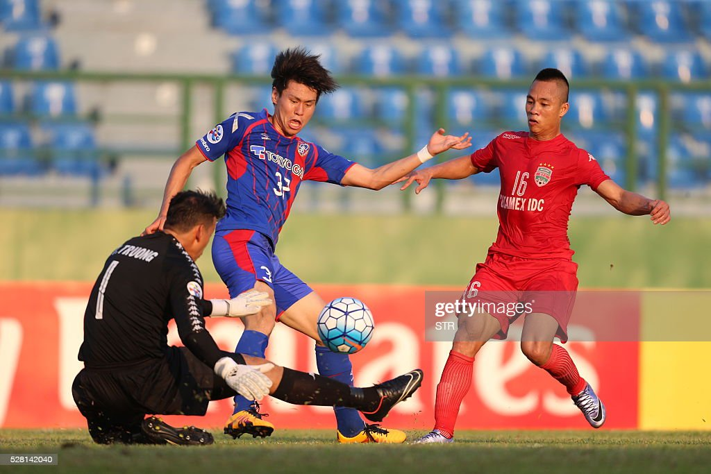 Hashimoto Kento (C) of Japan's FC Tokyo chalenges goal keeper Bui Tan Truong (L) of Vietnam's Becamex Binh Duong during a AFC Championship Group E football match on May 4, 2016 in Thu Dau Mot city, southern province of Binh Duong. FC Tokyo won 2-1. / AFP / STR