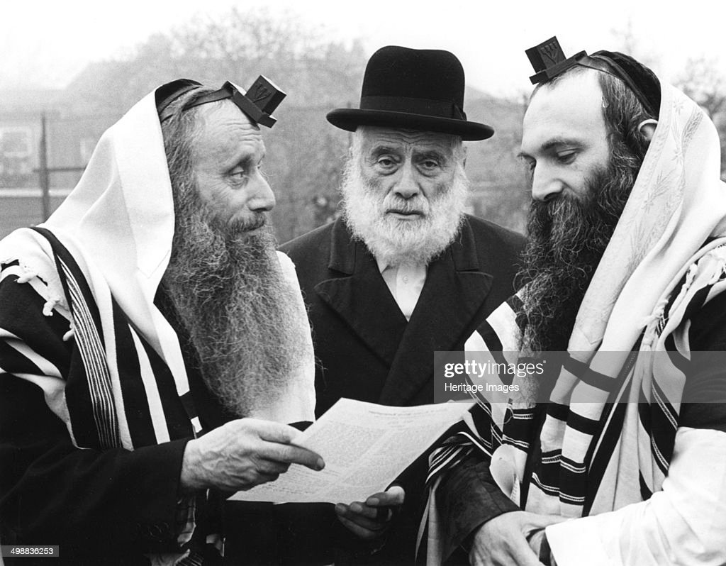 Hasidic Jews wearing tefillin and tzitzit, 1981. Tefillin are small boxes containing passages of religious text written on parchment scrolls. They are attached with leather straps, and worn during prayer. Tzitzit are woven shawls.