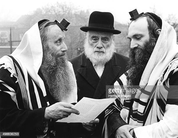 Hasidic Jews wearing tefillin and tzitzit 1981 Tefillin are small boxes containing passages of religious text written on parchment scrolls They are...