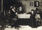 Hasidic men and boy sitting at table Russian postcard from early 20th century