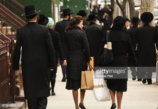 Hasidic men and women walk through a Jewish Orthodox neighborhood in Brooklyn on April 24 2017 in New York City According to a new report released by...