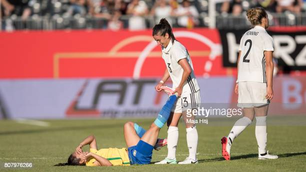 Hasret Kayikci of Germany helps Leticia Santos of Brazil during the Women's International Friendly match between Germany and Brazil at BWTStadion am...