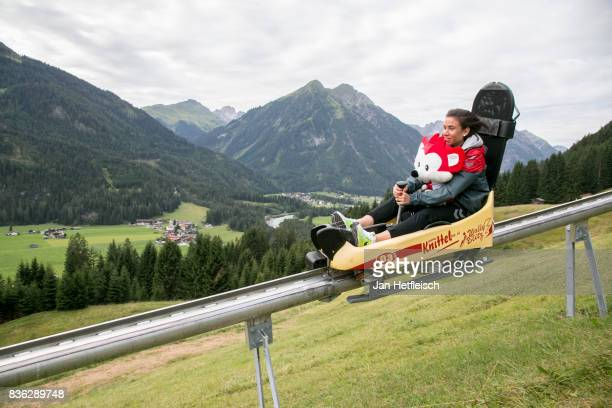 Hasret Kayikci of SC Freiburg runs down the summer toboggan run with 'Fuechsle' the mascot during the Allianz Frauen Bundesliga Club Tour on August...
