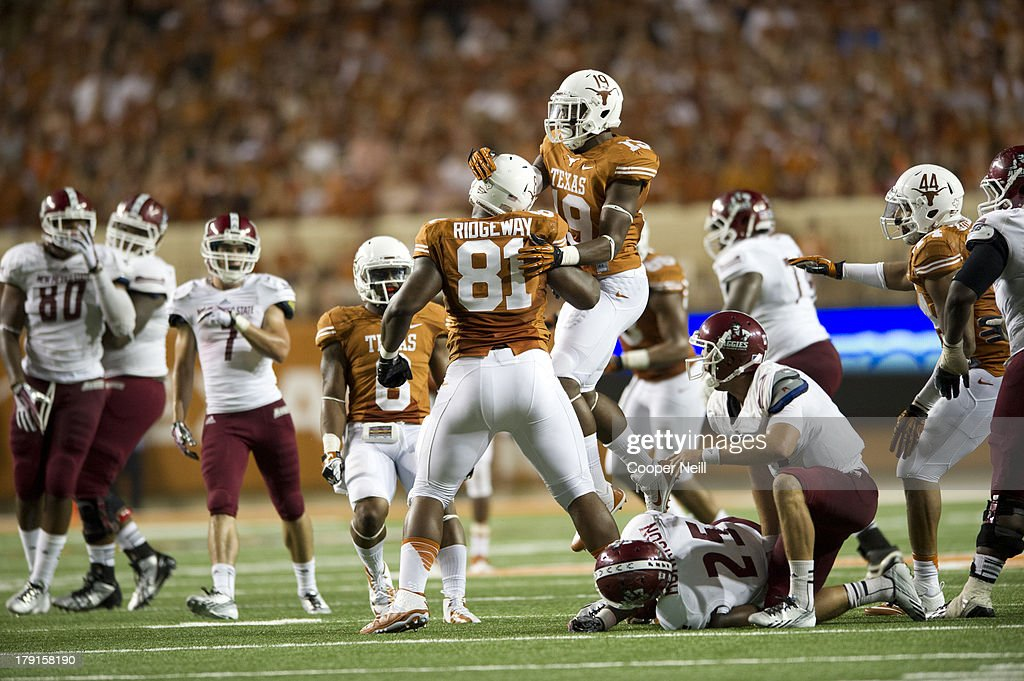 Hassan Ridgeway #81 of the Texas Longhorns celebrates with teammates after making a tackle for a loss of yards against the New Mexico State Aggies on August 31, 2013 at Darrell K Royal-Texas Memorial Stadium in Austin, Texas.
