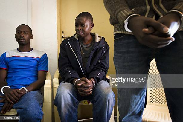 Hassan Ruyima and two other men appear in handcuffs as they are presented to journalists by the Ugandan military on August 12 2010 Four men were...
