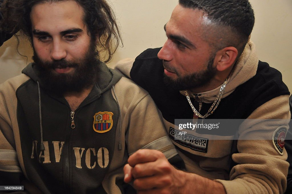 Hassan Srour, a Lebanese citizen who was captured by Syrian security forces after infiltrating the country to fight alongside rebel forces, listens to his one his relatives after his release in the Lebanese northern city of Tripoli on March 21, 2013. Srour is officially the only survivor of a group composed of young Sunni Lebanese and a Palestinians from Tripoli, in northern Lebanon, who tried to enter Syria in November.