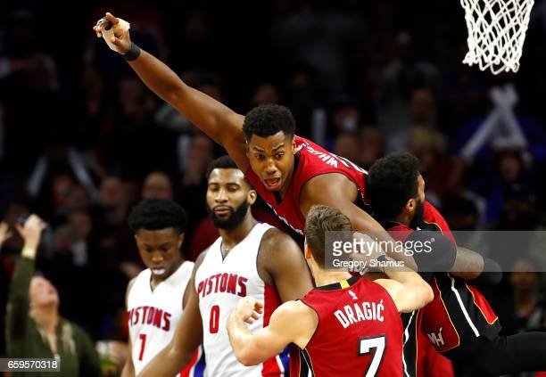 Hassan Whiteside of the Miami Heat celebrates his buzzer beating game winning basket with teammates in front of Andre Drummond of the Detroit Pistons...