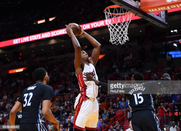 Hassan Whiteside of the Miami Heat dunks over Shabazz Muhammad of the Minnesota Timberwolves during the second half of the game at American Airlines...