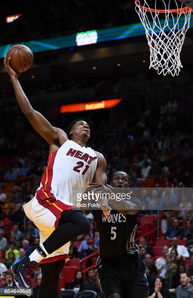 Hassan Whiteside of the Miami Heat dunks past Gorgui Dieng of the Minnesota Timberwolves during the second half of the game at American Airlines...