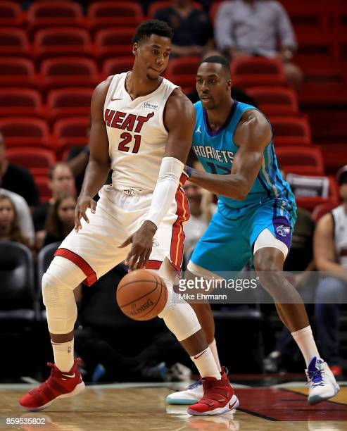 Hassan Whiteside of the Miami Heat posts up Dwight Howard of the Charlotte Hornets during a preseason game at American Airlines Arena on October 9...