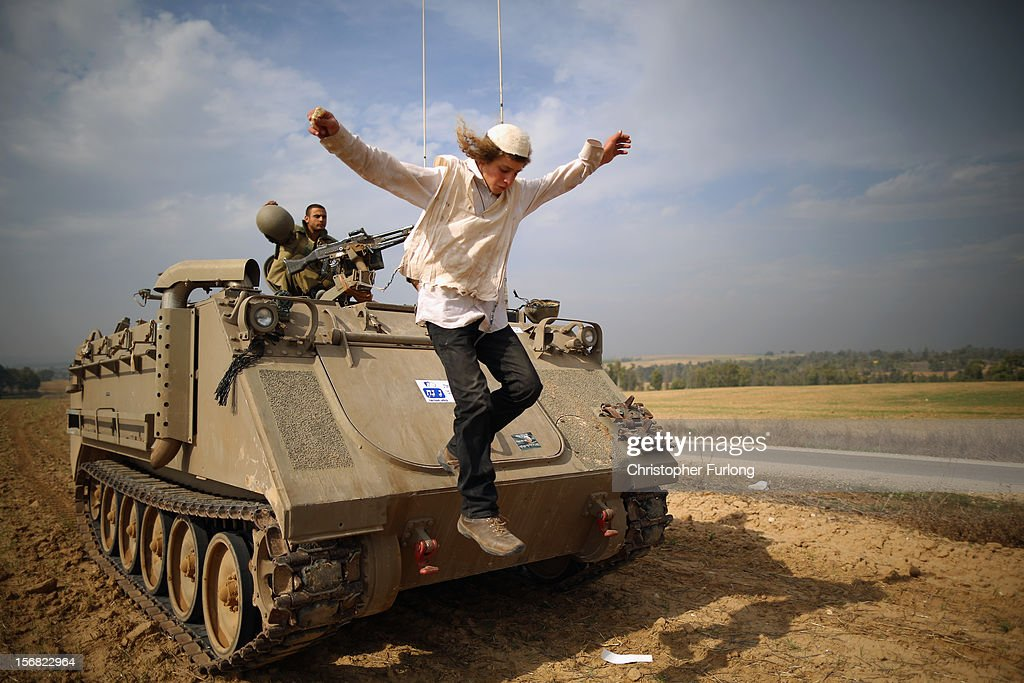 A Hassidic Jewish boy jumps off an APC after dancing on the vehicle to show support with jubilant Israeli soldiers at the border with the Gaza Strip on November 22, 2012 close to the northern Gaza Strip border with Israel. The ceasefire between Israel and Hamas appears to be holding despite rockets being fired on Israel from Gaza. During the night the IDF reportedly arrested a number of 'terror operatives' in the West Bank in continued efforts to restore peace in the region.