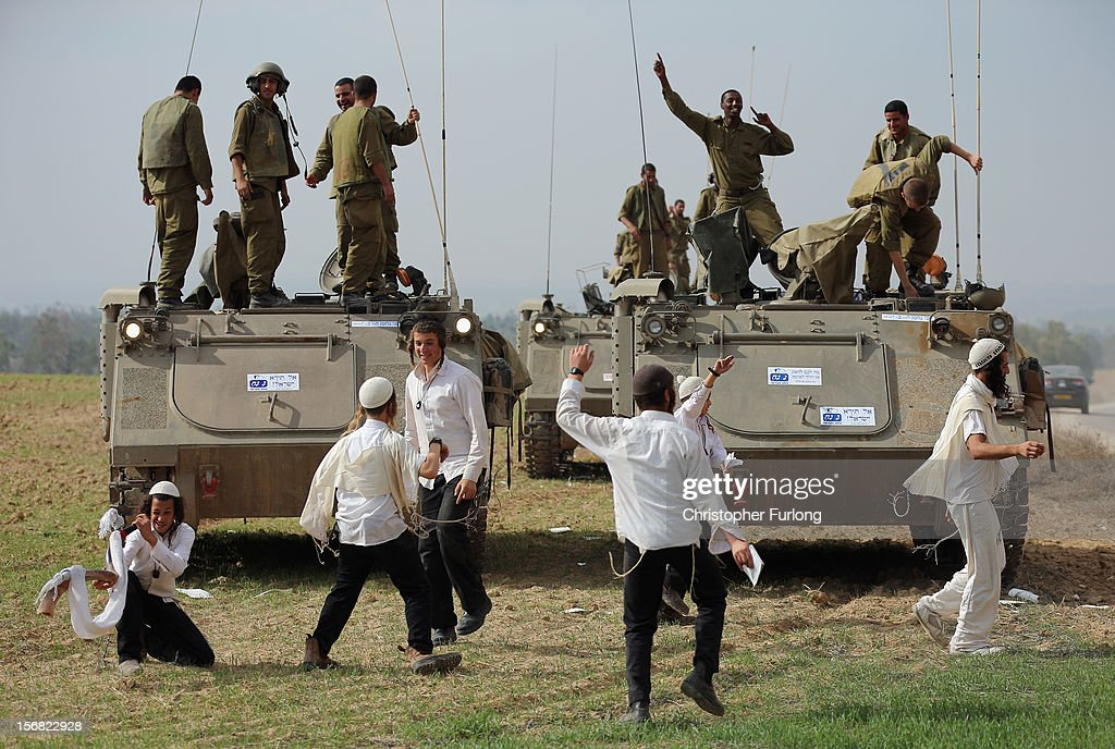 Hassidic Jewish boys dance as they show their support with Israeli soldiers at the border with the Gaza Strip on November 22, 2012 close to the northern Gaza Strip border with Israel. The ceasefire between Israel and Hamas appears to be holding despite rockets being fired on Israel from Gaza. During the night the IDF reportedly arrested a number of 'terror operatives' in the West Bank in continued efforts to restore peace in the region.