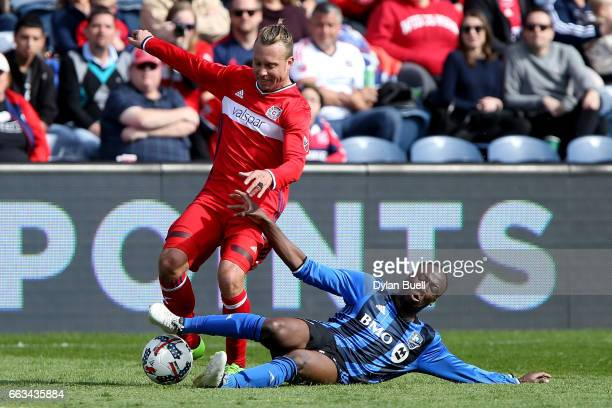 Hassoun Camara of Montreal Impact tackles the ball from Michael Harrington of Chicago Fire in the second half during an MLS match at Toyota Park on...
