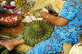 polynesian lady making a hat with leaves