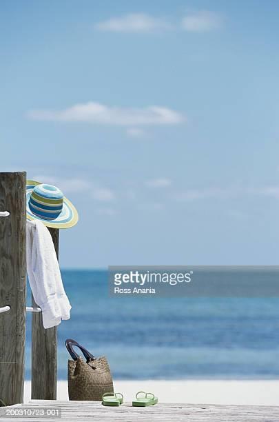 Hat, towel, tote bag, and flip-flops at end of boardwalk at beach