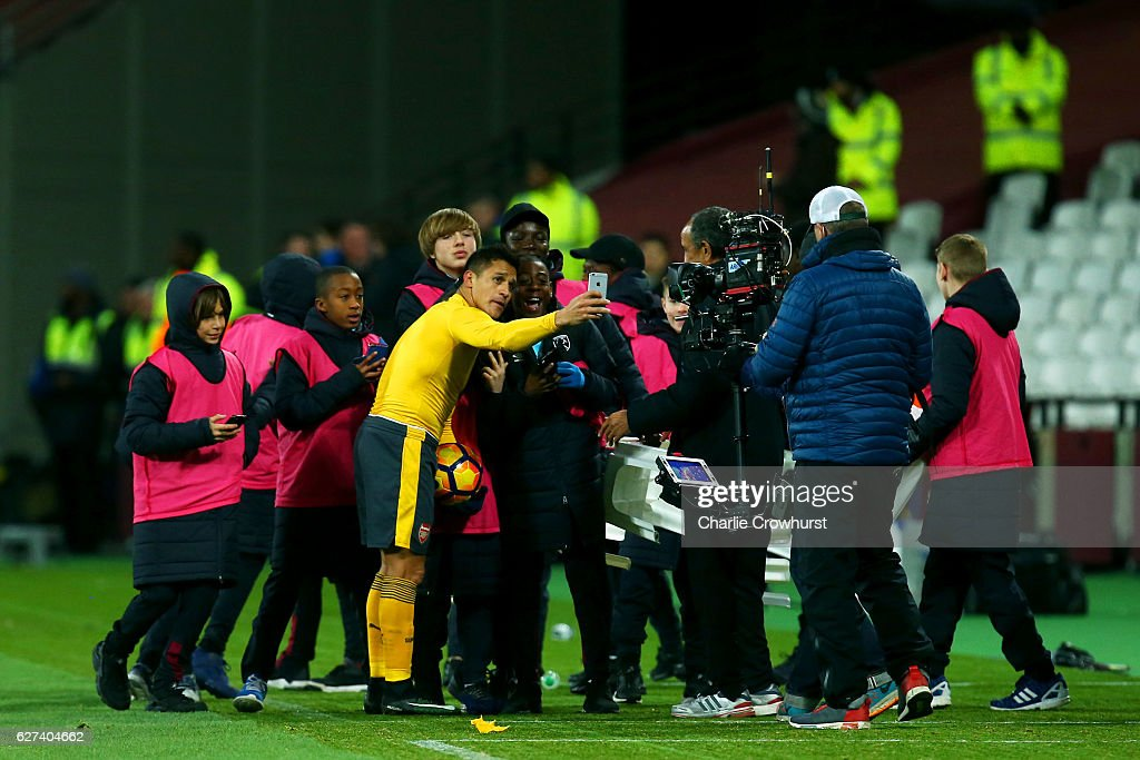 Hat trick hero Alexis Sanchez of Arsenal poses for a selfie photograph with ball kids after the Premier League match between West Ham United and Arsenal at London Stadium on December 3, 2016 in London, England.