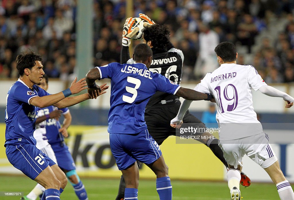 Hatami (L) challenges UAE's Al-Ain goalkeeper Dawoud Sulaiman catches the ball as Iran's Esteghlal midfielder Jlloyd Samuel (C) and Al-Ain's defender Mohanad Salem (R) vie during their AFC Champions League group D football match at Azadi stadium in Tehran on March 13, 2013.