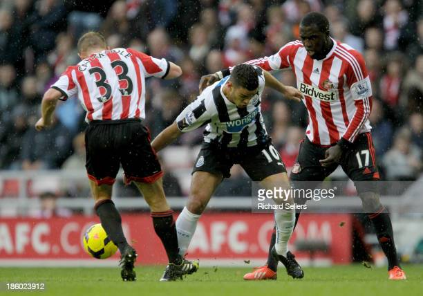 Hatem Ben Arfa of Newcastle is challenged by Lee Cattermole and Jozy Altidore of Sunderland during the Barclays Premier League match between...