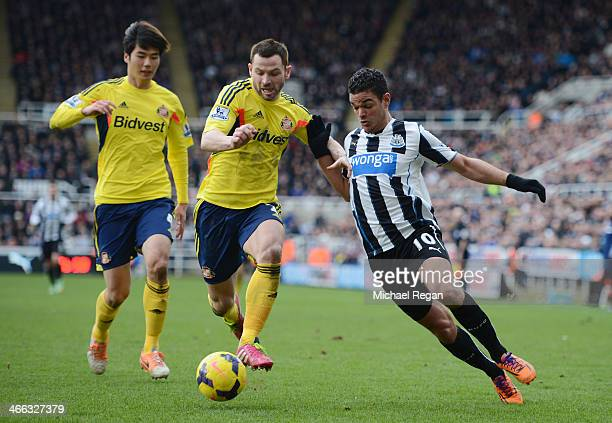 Hatem Ben Arfa of Newcastle is challenged by Phil Bardsley and Ki SungYong of Sunderland during the Barclays Premier League match between Newcastle...