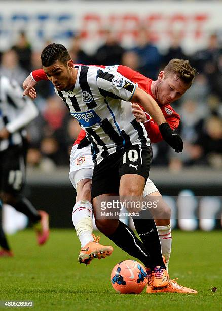 Hatem Ben Arfa of Newcastle is tackled Aron Gunnarsson of Cardiff during the Budweiser FA Cup third round match between Newcastle United and Cardiff...