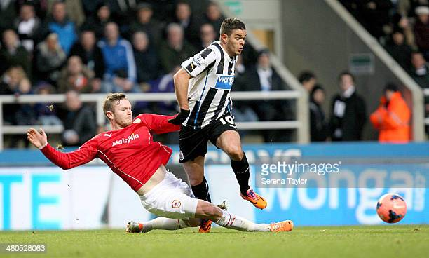 Hatem Ben Arfa of Newcastle is tackled by Aron Gunnarsson of Cardiff during the Budweiser FA Cup third round match between Newcastle United and...